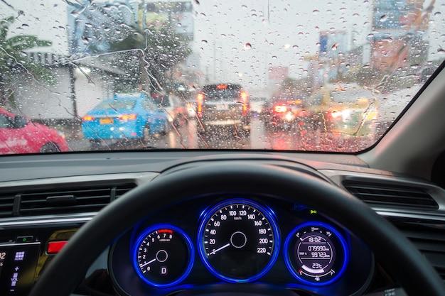 ラッシュアワー時の渋滞梅雨時の交通渋滞で運転中の車の手道路交通時の雨天時 Premium写真