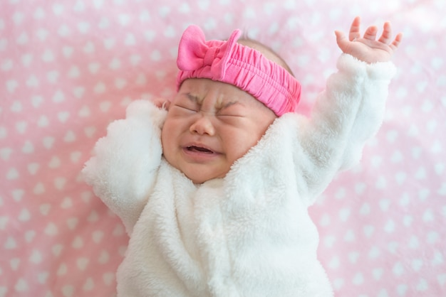 Плакать новорожденной девочке носить свитер и розовое оголовье на кровати Premium Фотографии