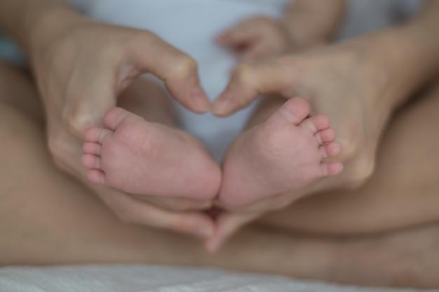 母の手で赤ちゃんの足。ママと彼女の子供。幸せな家族の概念。マタニティの美しい概念図 Premium写真