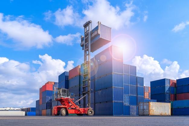 ロジスティックインポートエクスポートビジネス用の産業用コンテナヤード、貨物コンテナスタックを備えたロジスティックシップヤードで貨物用コンテナボックスを処理するフォークリフト Premium写真