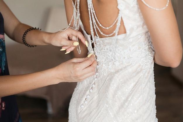 ガールフレンドのボタンを押すのを助ける白い花嫁介添人ドレス Premium写真