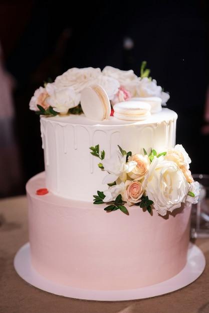 マカロンとバラの美しいケーキがテーブルの上に立つ Premium写真