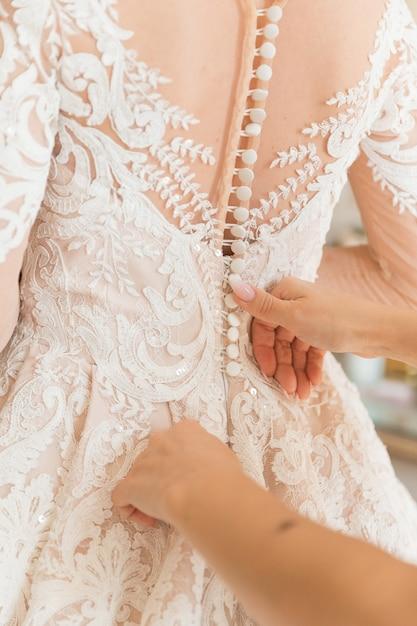 花嫁介添人にボタンを押された花嫁の白いドレス Premium写真
