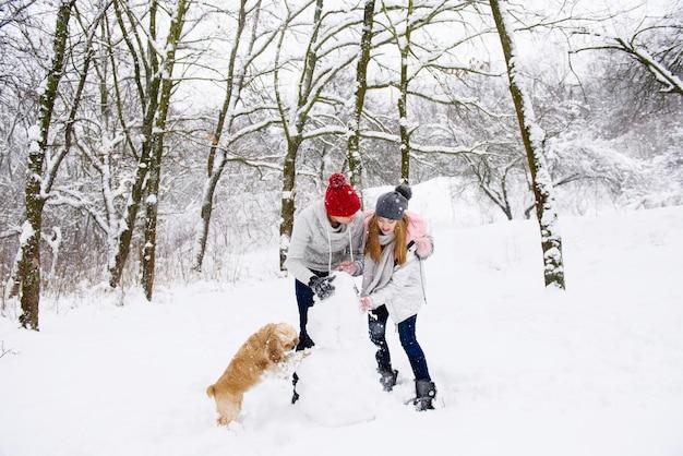 Пара делает снеговика с собакой в зимнем лесу Premium Фотографии