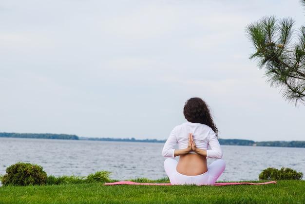 Молодая беременная женщина занимается йогой на открытом воздухе Premium Фотографии
