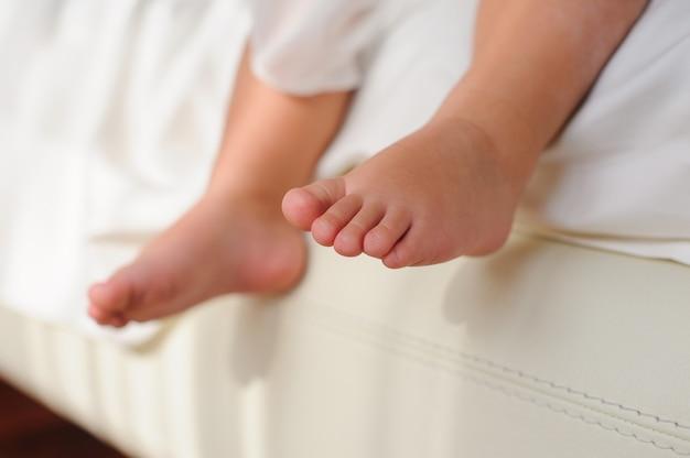 Детские босые ноги, сидя на кровати Premium Фотографии