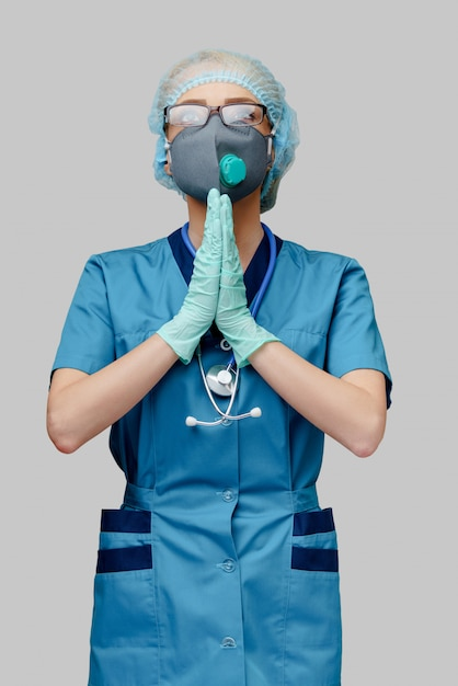 Врач медсестра женщина носить защитную маску и латексные перчатки - молиться над надеждой жест Premium Фотографии