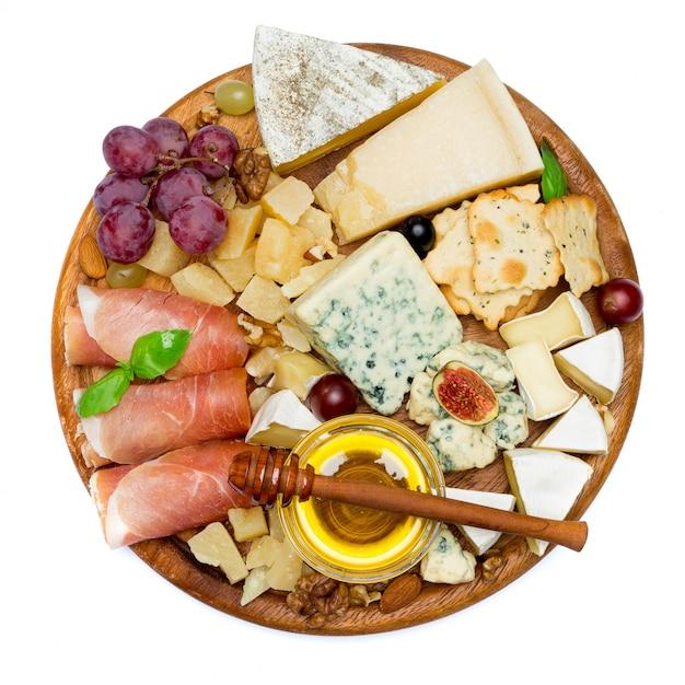Сыр камамбер и прошутто с медом, инжир, грецкие орехи на деревянной доске Premium Фотографии