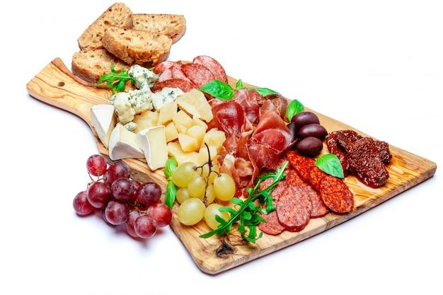 Холодная мясная сырная тарелка с колбасой салями, прошутто и сыром Premium Фотографии