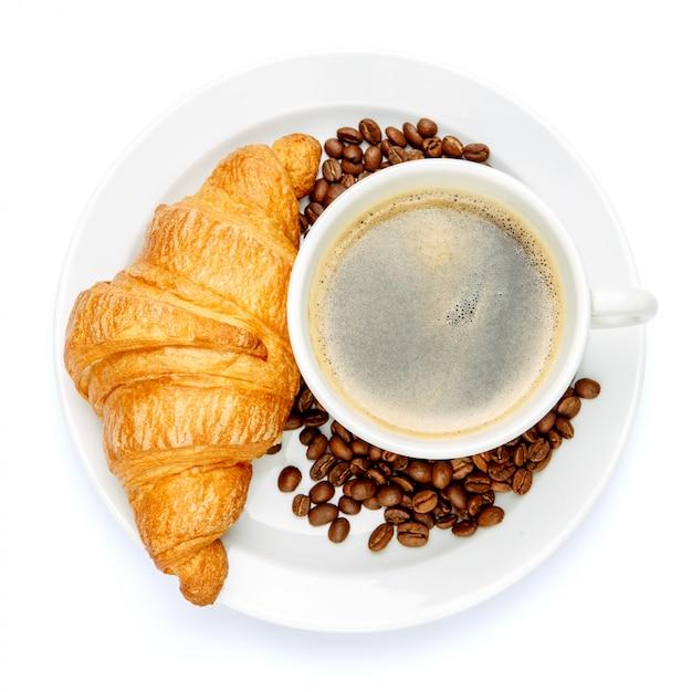 Свежий круассан и кофе на белом фоне Premium Фотографии