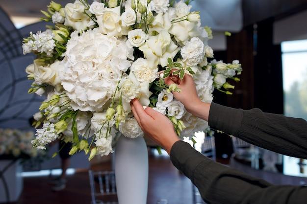 Процесс оформления большого букета белых роз Premium Фотографии
