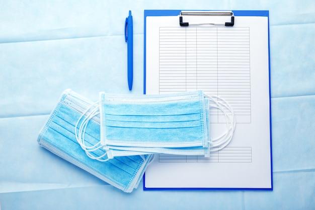 Назначение врача. медицинский тест формирует документы и медицинские маски, маски хирургической защиты на синем фоне. Premium Фотографии