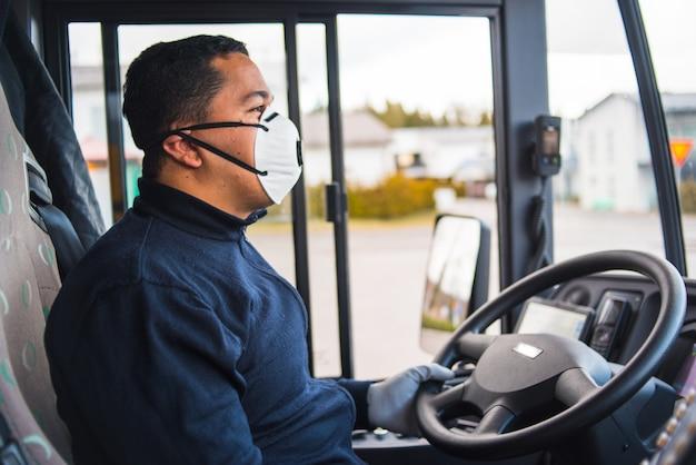 Автобус с защитной маской и перчатками за рулем междугороднего автобуса Premium Фотографии