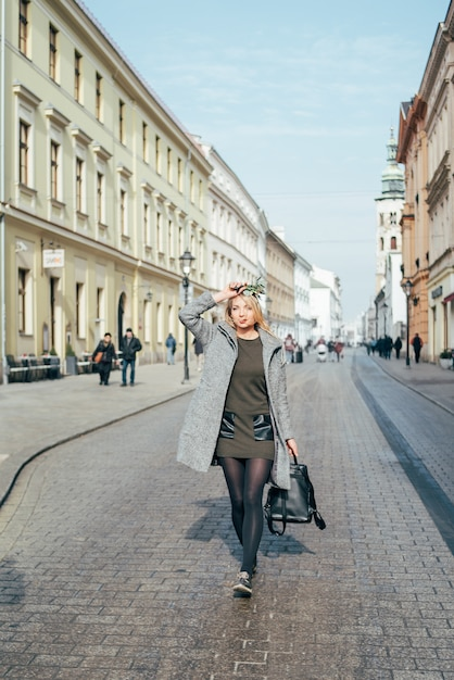 灰色のコート、濃い緑色のショートドレス、街の通りを歩く黒タイツの美しい若いブロンドの女性。 Premium写真