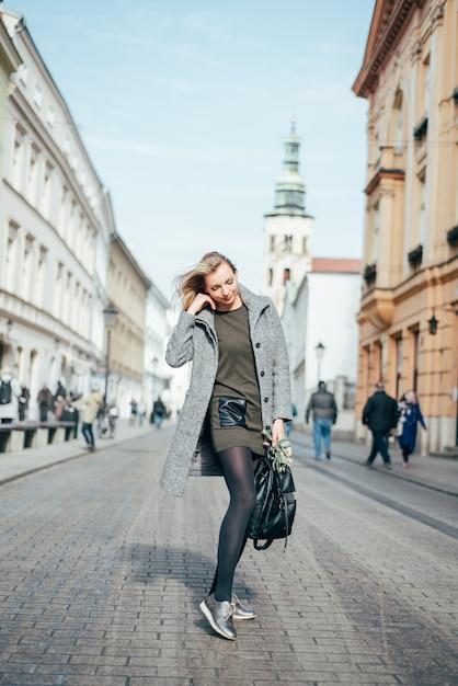 灰色のコート、濃い緑色のショートドレス、街の通りを歩いて黒タイツの若い美しいブロンドの女性。 Premium写真