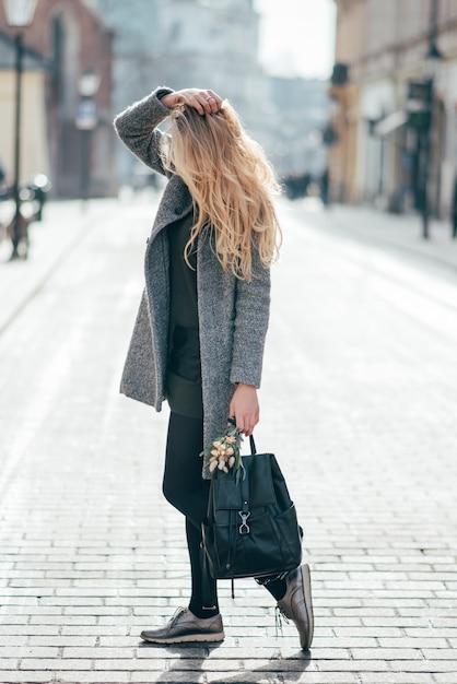 長いブロンドのウェーブのかかった髪の若いかなりブロンドの女性は通りにいて、彼女のブロンドの髪、バックパック、花束を保持しています。 Premium写真