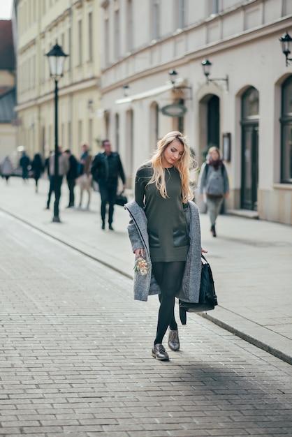 灰色のコート、ダークグリーンのショートドレス、街の通りを歩く黒のタイツを身に着けている白人の美しい若いスタイリッシュなブロンドの女性。 Premium写真