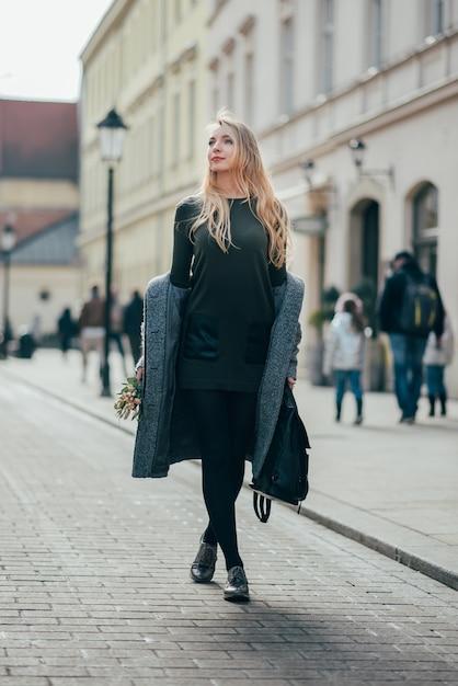 通りを歩いて、バックパックと花束を保持している長いブロンドのウェーブのかかった髪の白人のかなり金髪の若い女性。 Premium写真