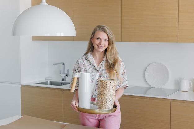 Молодая блондинка в розовой одежде держит в руках садовый инвентарь Premium Фотографии