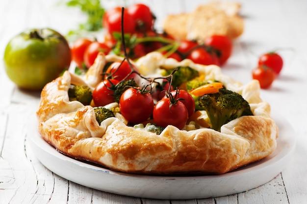 Вегетарианский пирог с брокколи, помидорами, перцем и сыром Premium Фотографии