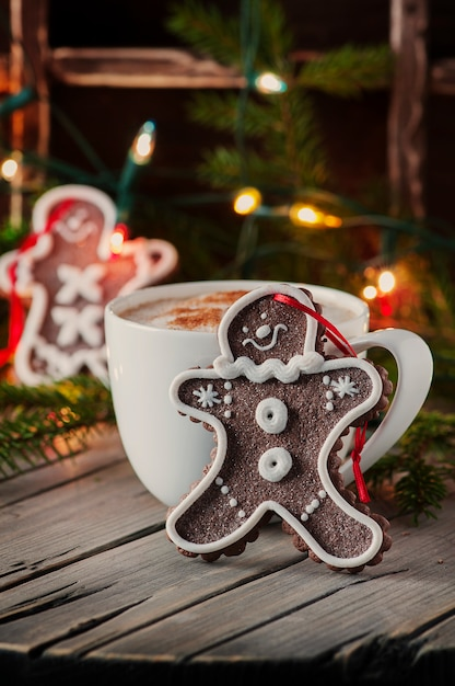 木製のテーブルにコーヒーのカップとジンジャーブレッド Premium写真