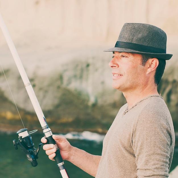 Красивый мужчина, рыбалка во время выходного дня Premium Фотографии