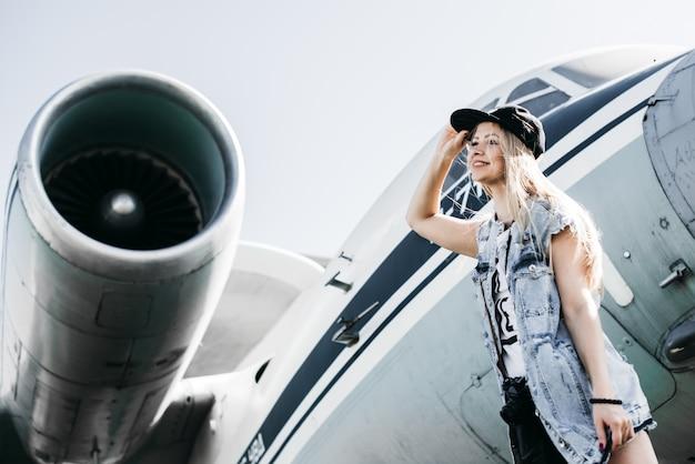 Красивая женщина-турист позирует возле самолета против реактивного двигателя, держа руку на лбу, глядя вдаль, ожидая чего-то или кого-то Premium Фотографии