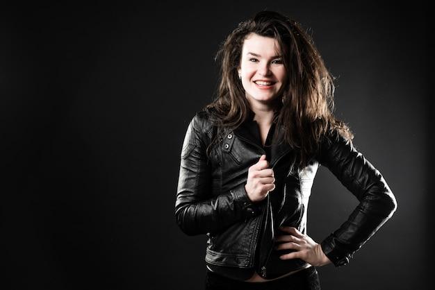 Красивая брюнетка девушка в черном пиджаке позирует в студии на темном фоне. Premium Фотографии