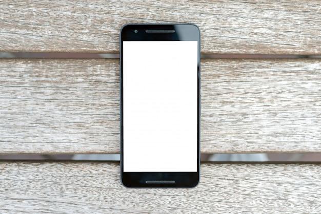 木製の背景に白い画面でモバイルスマートフォンモックアップ。 Premium写真