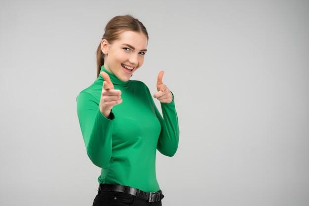 指を指しているカメラを見て幸せな陽気な若い女の子 Premium写真