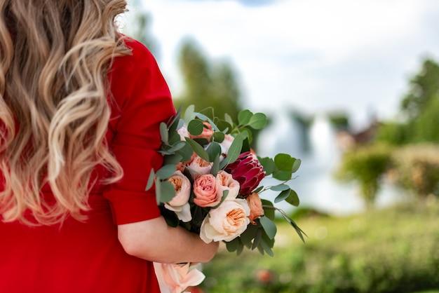 巻き毛を持つブロンドの女性は彼女の手で美しい色の花束を持っています、 Premium写真
