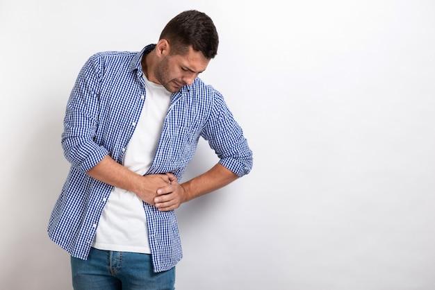 Больной мужчина с болями в животе, держась за живот Premium Фотографии