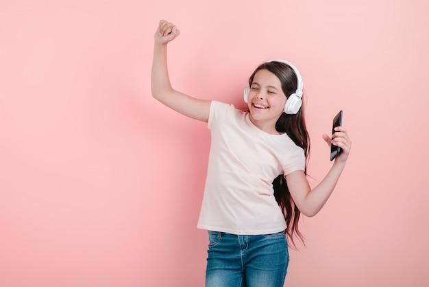 電話をかざして手で音楽を聴くイヤホンで目を閉じて踊っている女の子 Premium写真