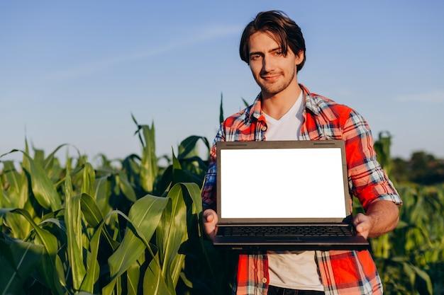 農夫は開いているラップトップを保持しているフィールドに立っています。ホワイトスクリーンモックアップ Premium写真