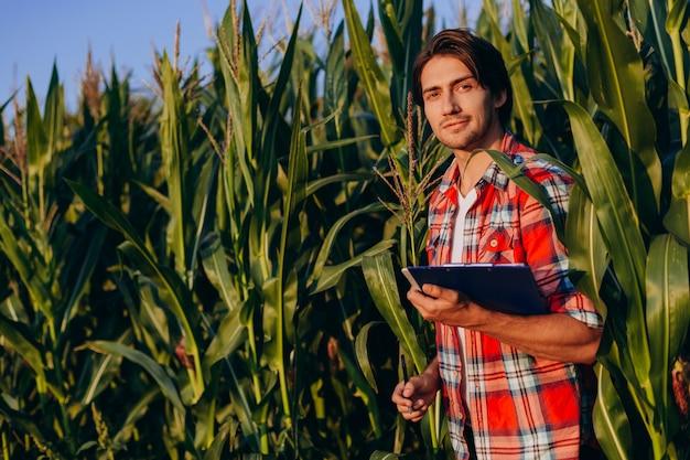 トウモロコシ畑に立って、カメラを見て幸せな農学者の肖像画。 Premium写真