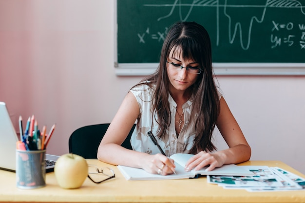 Женщина учитель в очках, написание сидя за столом. Premium Фотографии