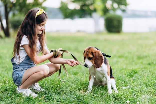 小さな女の子が犬と一緒に座って、花の匂いを嗅ぎます。 Premium写真