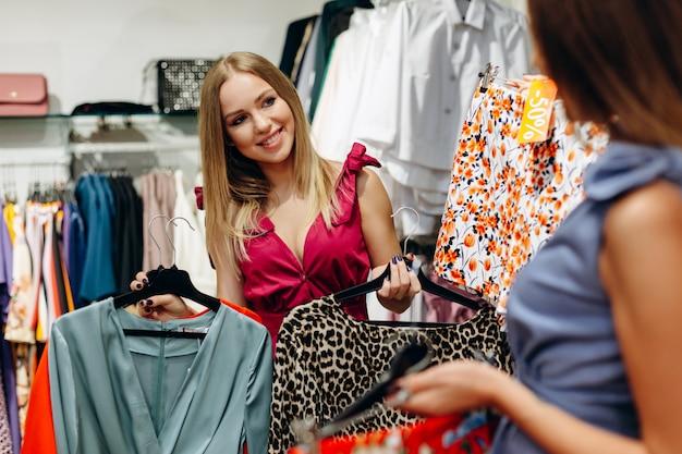 Модный продавец показывает платье и тигровую блузку девушке Premium Фотографии