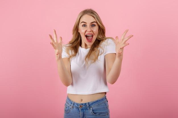 ピンクの背景の上に立って興奮して叫んでいる若い女性のイメージ。カメラを探しています。 Premium写真