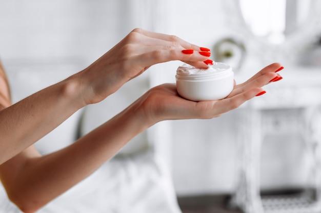白い背景で隔離のクリームの瓶を保持している美しい若い女性の手 Premium写真