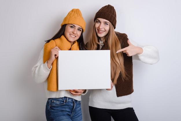 Красивый молодой студент девушки держит белый квадрат чистый лист в ее руках. Premium Фотографии