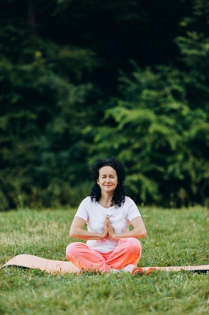 ヨガに座っている年配の女性は、ヨガマットにポーズし、ジェスチャーナマステを作ります。 Premium写真