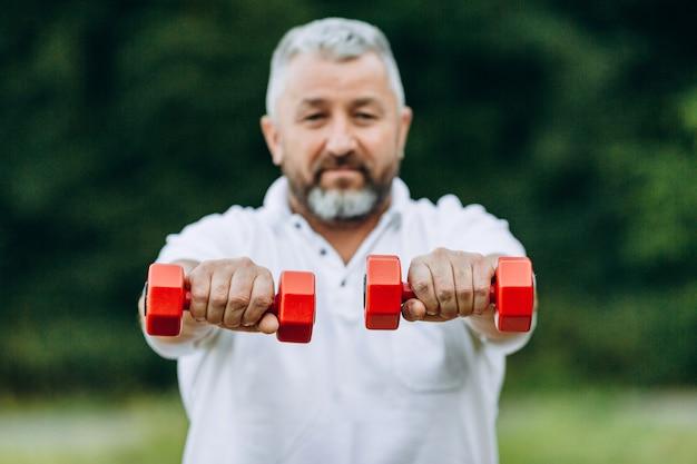 まっすぐな手でダンベルを持って立っている年配の男性。焦点のダンベル Premium写真