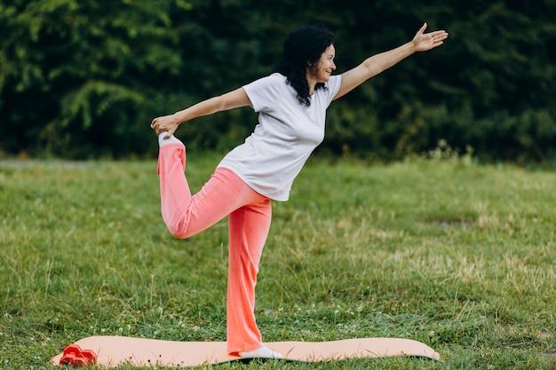 Женщина среднего возраста делая представление йоги держа ее ногу внешний. спорт Premium Фотографии
