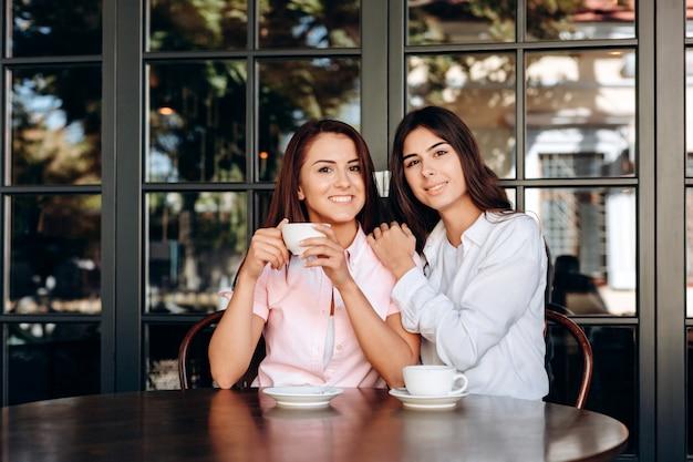 コーヒーを飲みながらカフェで美しくポーズをとって若いブルネット Premium写真