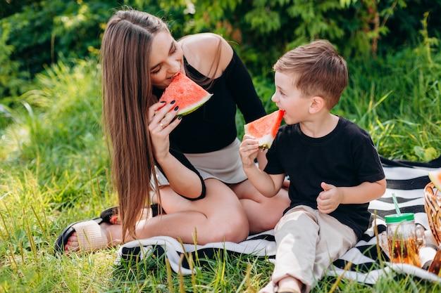 Мать и сын на пикнике в парке едят арбуз. Premium Фотографии