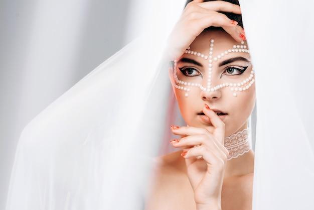 Модная женщина смотрит под вуалью, касается ее лица руками Premium Фотографии