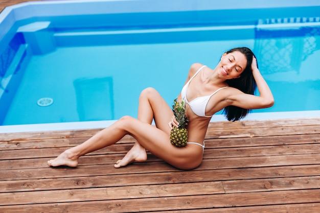 Красивая модель в купальнике позирует возле бассейна Premium Фотографии