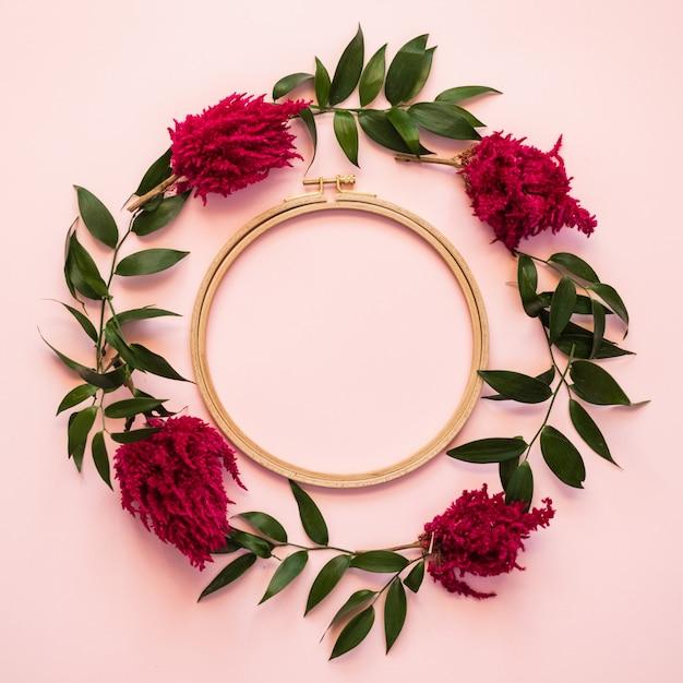 Крупным планом круг свежих цветов и зеленые листья лежат на розовом фоне - копией пространства Premium Фотографии