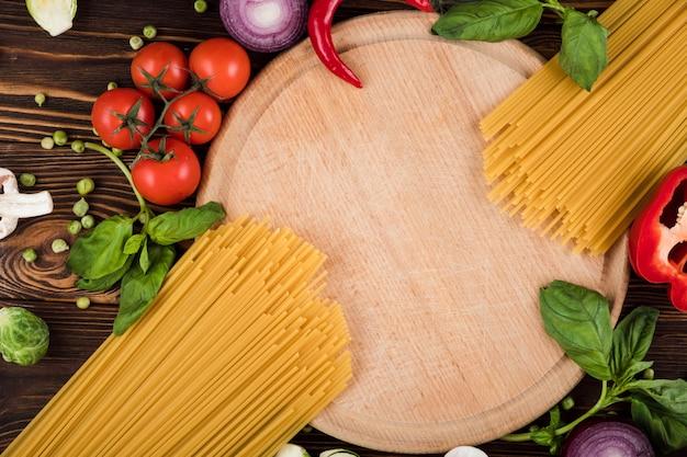 Спагетти на деревянной доске, вид сверху Premium Фотографии